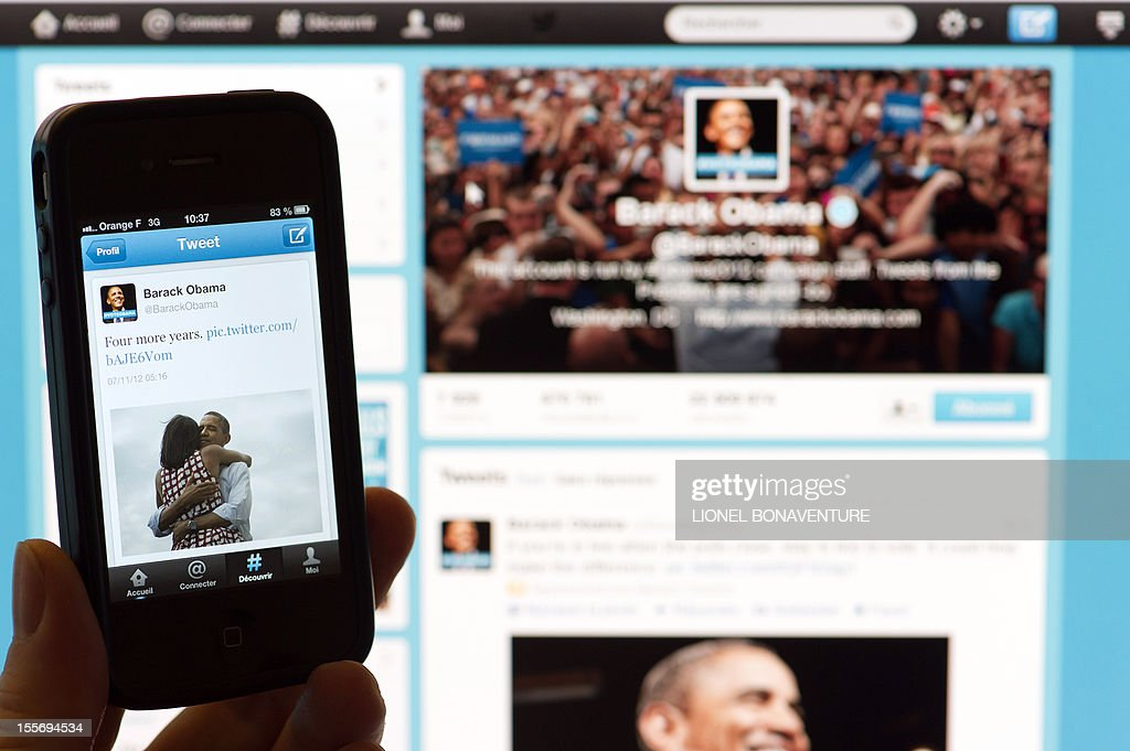 A person poses with a cell phone in front of a computer screen to check Barack Obama's tweet on November 7, 2012 in Paris after his re-election as US president. Barack Obama brought his sophisticated social media campaign to an emotional climax, proclaiming his victory on Twitter and Facebook just as TV networks were breaking the news. The post was his most re-tweeted -- 472,000 shares in three hours -- according to Twitter's politics account @gov. It was also the most popular ever, topping a message from singer Justin Bieber, website BuzzFeed said.