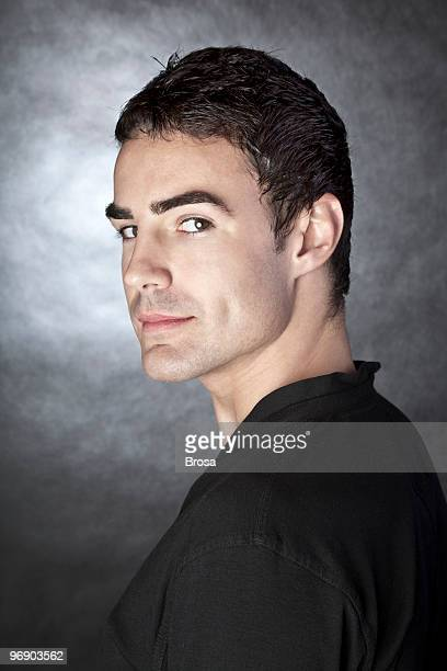 Person posing facing opposite direction in gray background