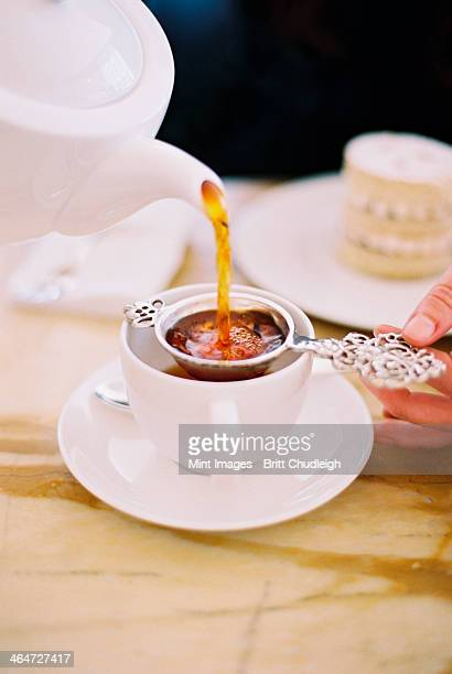 A person pouring a cup of tea, using a strainer. White china. Elegant afternoon tea.
