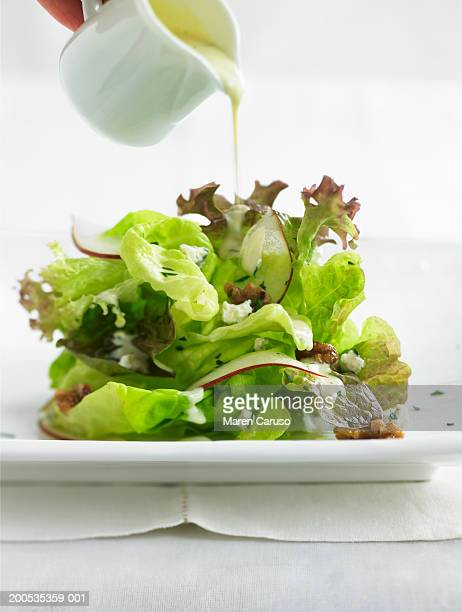 Person pouring dressing over salad with walnuts, radishes and feta