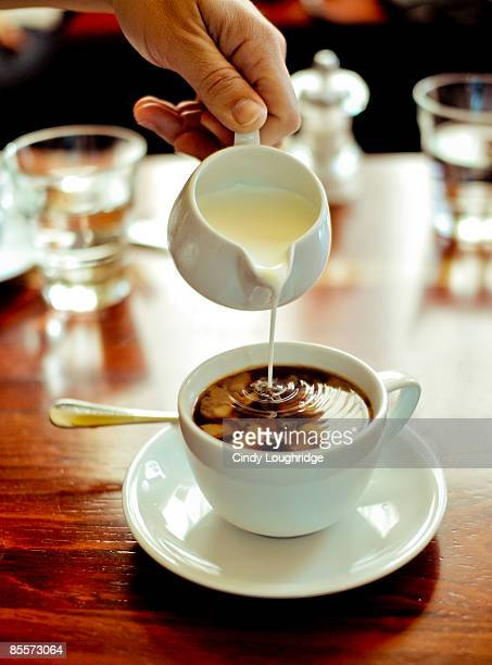 Person pouring milk into coffee cup