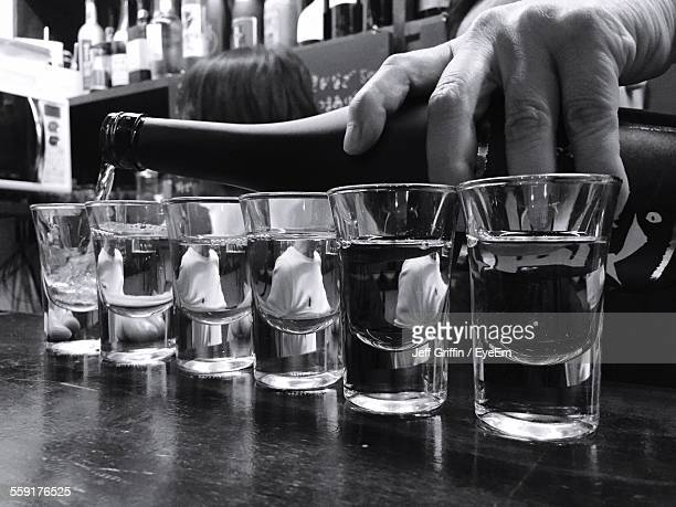 Person Pouring Tequila In Glasses