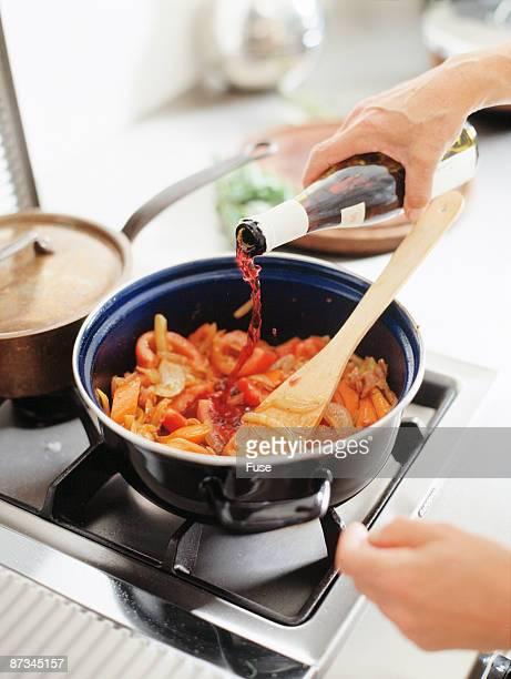 Person pouring wine in a saucepan