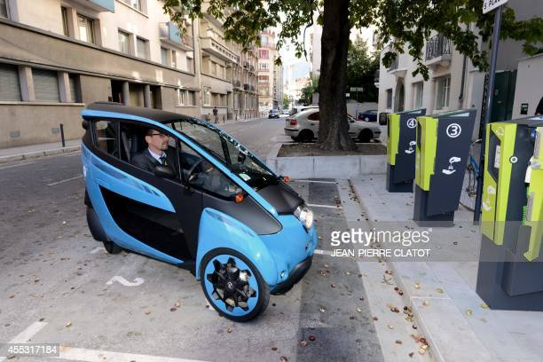 A person prepares to park with a Toyota threewheeled electricpowered car named the IRoad on September 12 2014 in Grenoble during the presentation of...