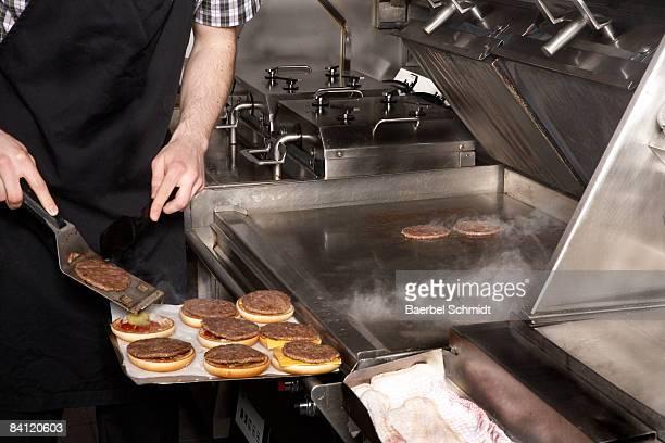 Person preparing Hamburger in Restaurant