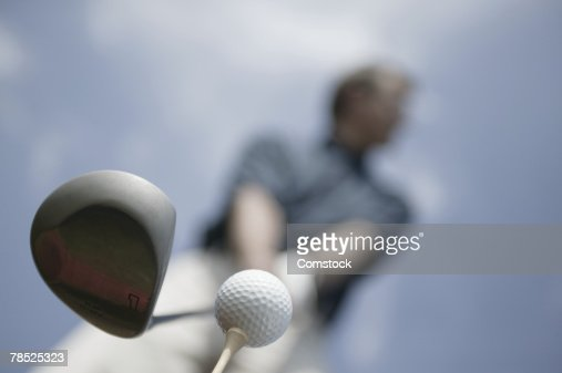 Person preparing to hit golf ball from tee