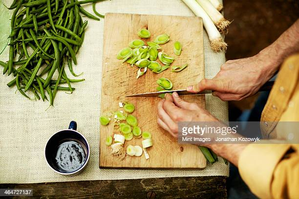 A person preparing vegetables, slicing spring onions on a chopping board.