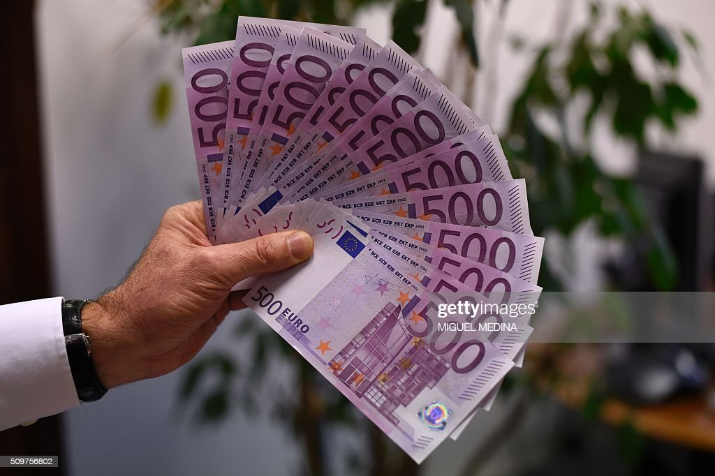 A person presents several 500 Euro notes on February 12, 2016 in Paris. The European Central Bank will take a decision soon on whether to keep printing 500-euro banknotes, with the arguments for doing so becoming 'less and less convincing', a top-ranking official said on February 11, 2016. / AFP / MIGUEL MEDINA