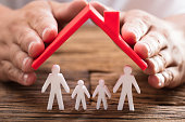 A person's hand protecting family figures with red roof on wooden desk