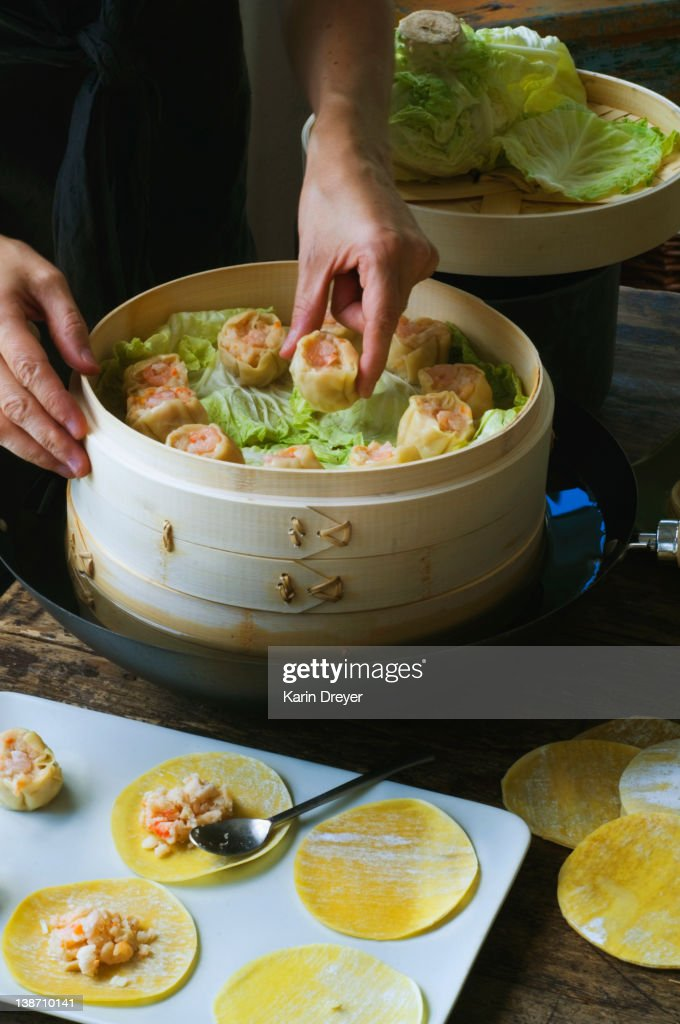 Person putting Asian dumplings in steamer with cabbage : Stock Photo