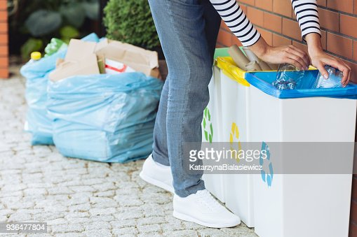 Person putting bottles into bin : Stock Photo