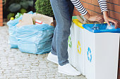Close-up of person putting plastic bottles into bin with blue symbol