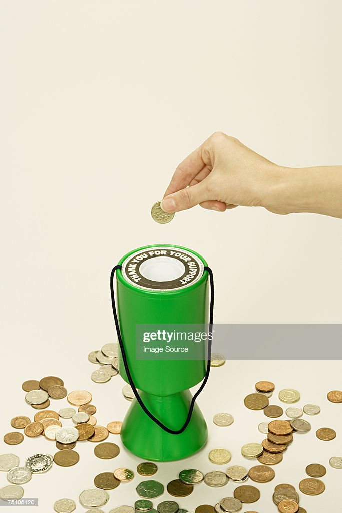 Person putting coin into donation box : Stock Photo
