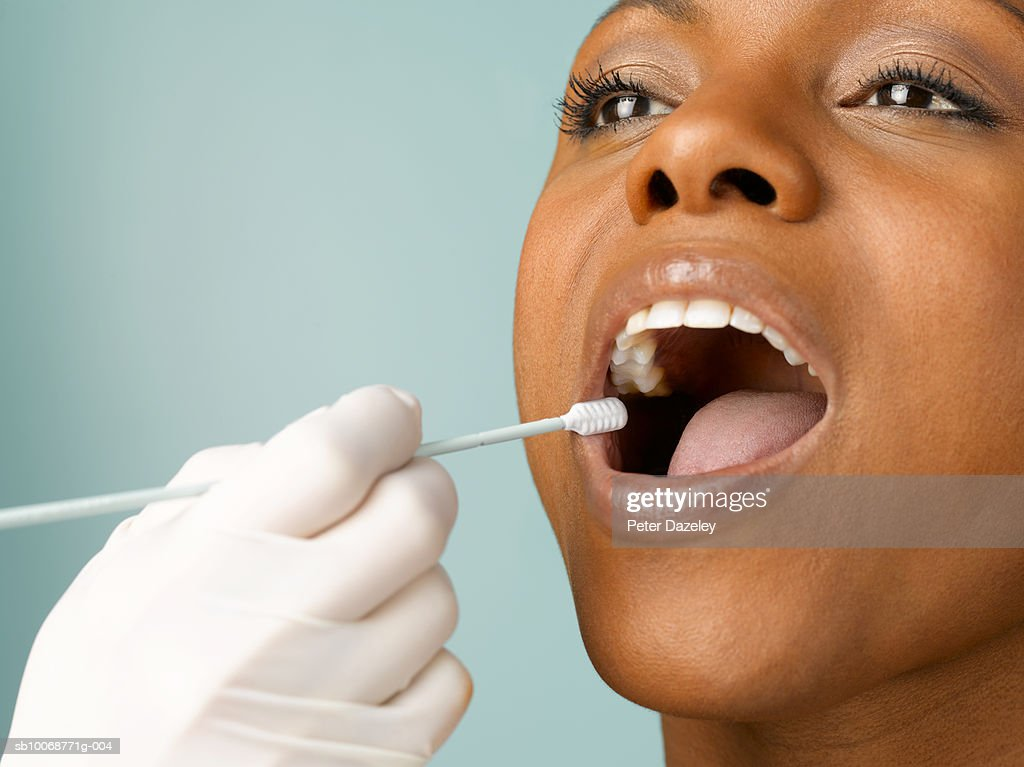 Person putting DNA test swab into woman's mouth, close up, studio shot : Stock Photo