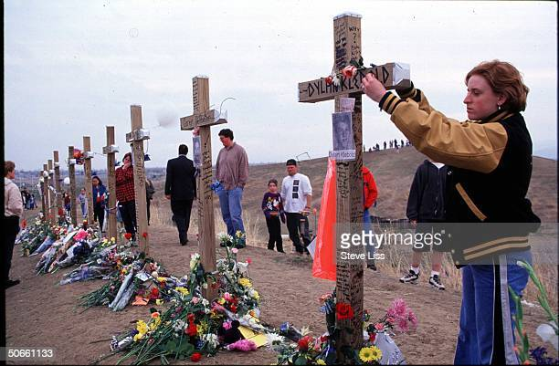 Person putting flowers on memorial cross for Dylan Klebold who w friend Eric Harris went on shooting spree at Columbine High School killing 13...