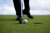Person putting golf ball, low section (differential focus)