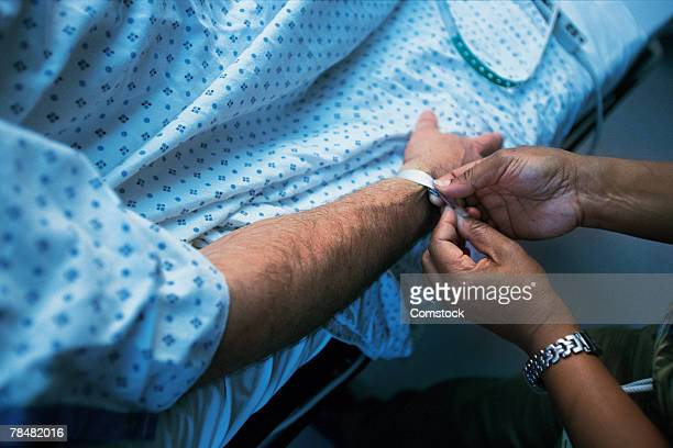Person putting id wristband on patient's arm