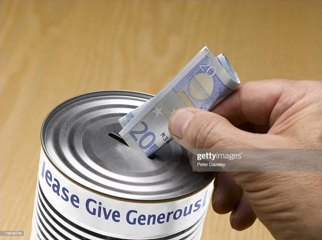 Person putting twenty Euro note into donation tin : Stock Photo