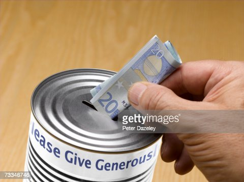 Person putting twenty Euro note into donation tin : Foto de stock