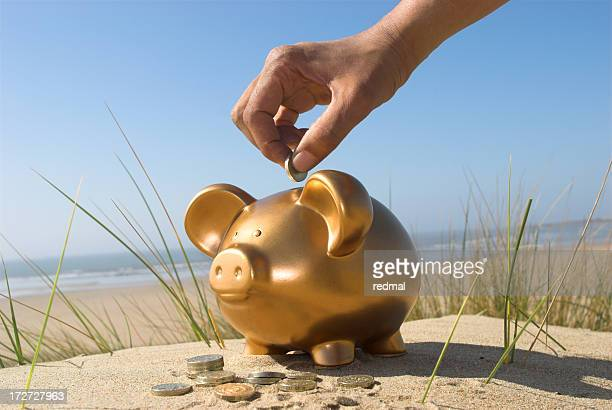 Person putting vacation savings into a golden piggy bank