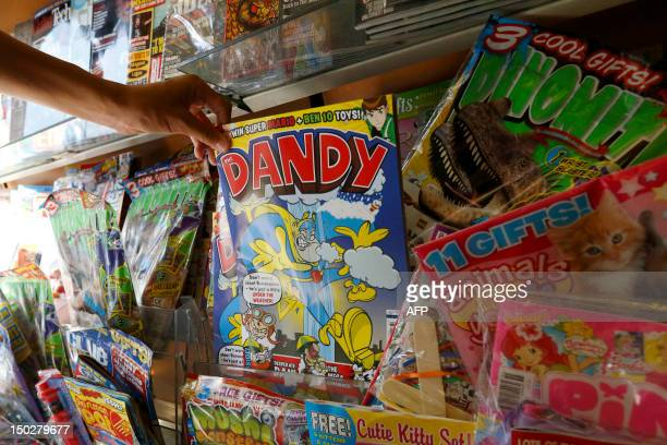 A person reaches for a copy of the children's comic The Dandy on the shelf of a news agent in central London on August 14 2012 Publishers DC Thompson...