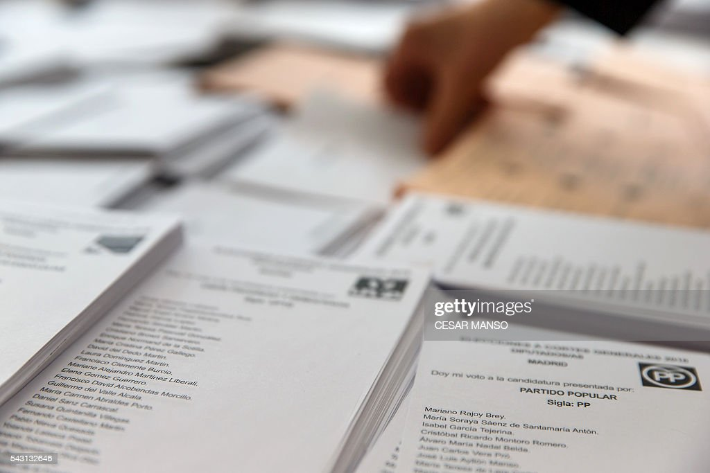 A person reaches for ballot paper of the Popular Party (PP) to vote in Spains general election at the Bernadette college polling station in Moncloa-Aravaca, Madrid, on June 26, 2016. Spain votes today, six months after an inconclusive election which saw parties unable to agree on a coalition government. MANSO