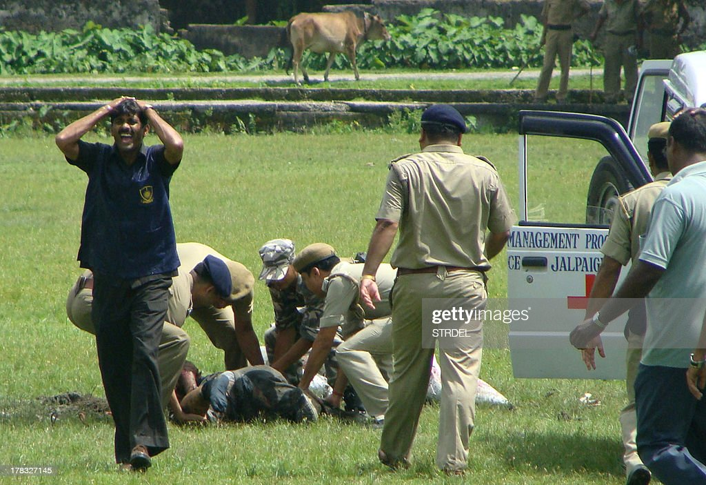 A person (L) reacts as police personnel tend to bomb disposal squad member L.B. Lohar, moments after he was killed while trying to defuse a bomb in Alipurduar, India's West Bengal state, on August 29, 2013. Lohar was killed while attempting to defuse bombs allegedly planted by the Kamtapuri Liberation Organisation (KLO) militants, a report said. AFP PHOTO/STR