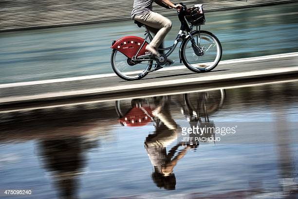 A person rides a bicycle of public bicycle sharing system Velo'v on May 28 2015 in a street of the central French city of Lyon The city is...