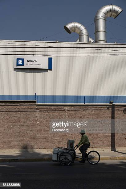 A person rides a bicycle past a General Motors Co assembly plant in Toluca de Lerdo Mexico on Saturday Jan 7 2017 Presidentelect Donald Trump slammed...