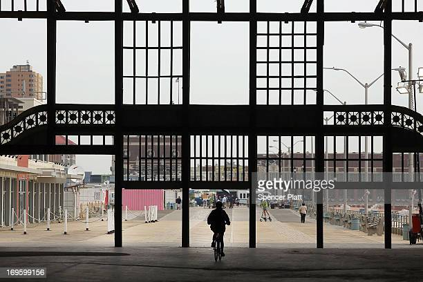 A person rides a bike down a new section of boardwalk before President Barack Obama spoke on May 28 2013 in Asbury Park New Jersey Seven months after...