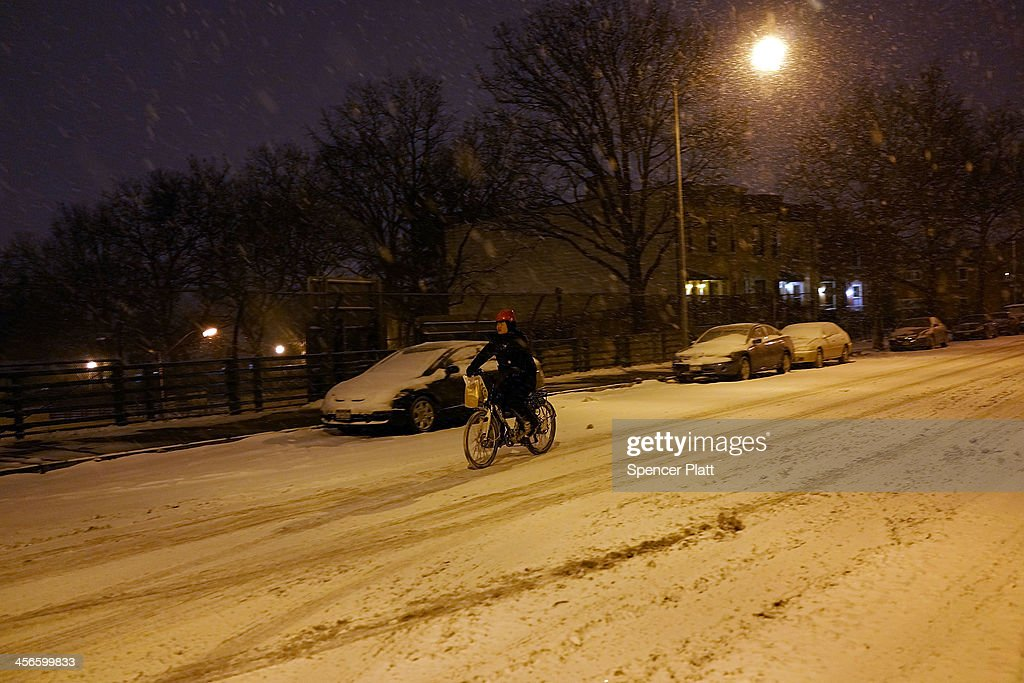 A person rides a bike during a snow storm on December 14, 2013 in the Brooklyn borough of New York, United States. Much of the Northeast was hit Saturday by a storm stretching over 1,000 miles that could result in at least a foot of snow on parts of New England.