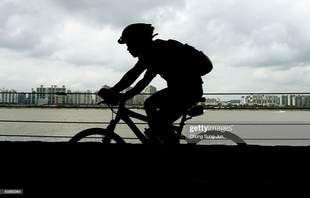 A person ridesa bike along the Han River on August 13 2005 in Seoul South Korea