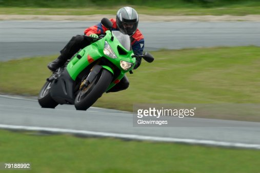 Person riding a motorcycle on a motor racing track : Foto de stock