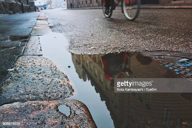 Person Riding Bicycle Against Buildings Reflecting On Puddle