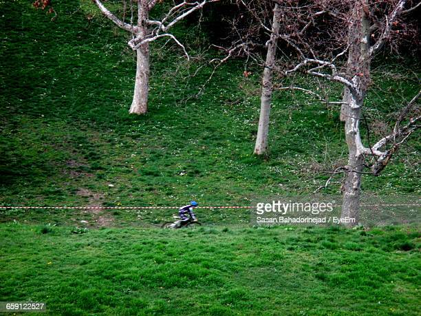 Person Riding Bicycle On Grassy Hill
