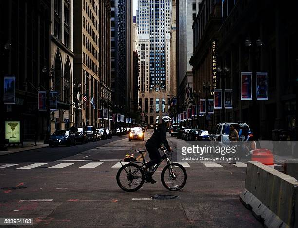 Person Riding Bicycle On Street At City