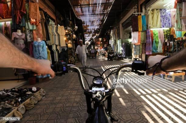 Person riding bike in street market, Medina, Marrakech, Morocco