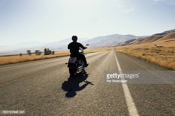 Person riding motorcycle, rear view