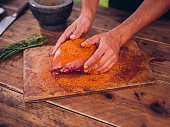Hands of a person rubbing some spicy dry seasoning into a fresh piece of raw pork on a wooden board
