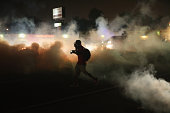 A person runs through a clowd of tear gas that police launched at demonstrators protesting the killing of teenager Michael Brown on August 17 2014 in...