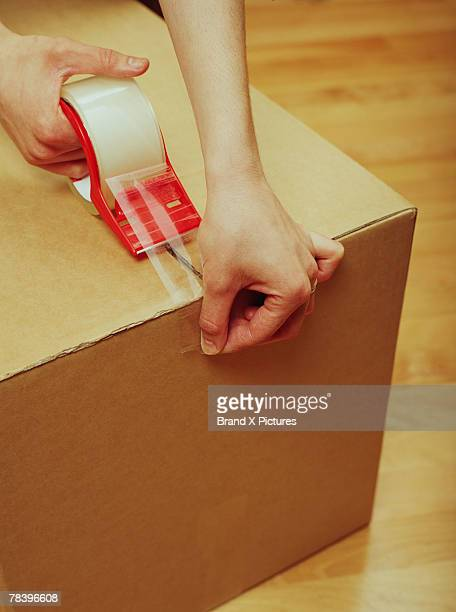 Person sealing box with packing tape