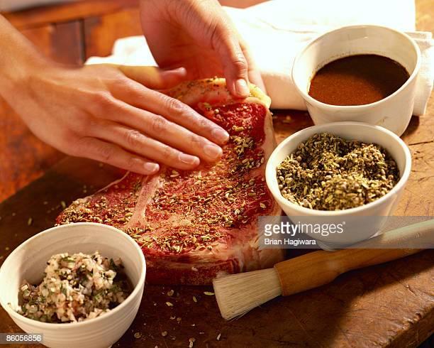 Person seasoning porterhouse steak