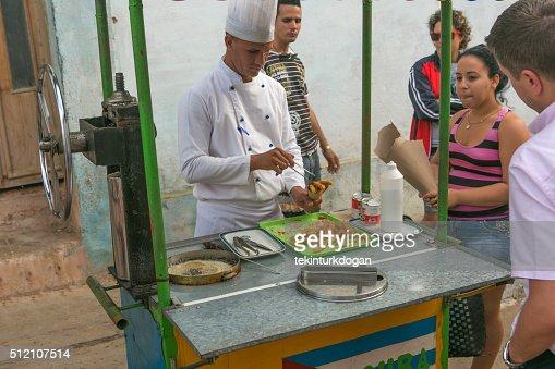 person selling sweet churros at street of trinidad cuba