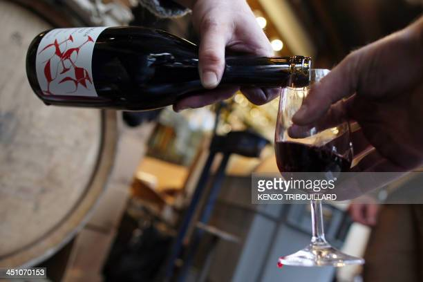 A person serves 2013 'Beaujolais Nouveau' wine on November 21 2013 in Paris From the heart of France to the foothills of Mount Fuji and the streets...