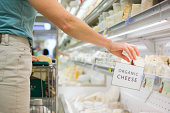 Person shopping for organic cheese