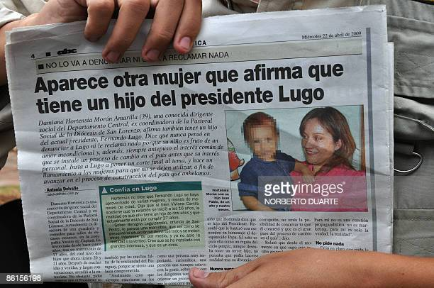 A person shows a newspaper with a portrait of Damiana Hortensia Morán Amarilla a 39year old daycare center director and her son in San Lorenzo 20...