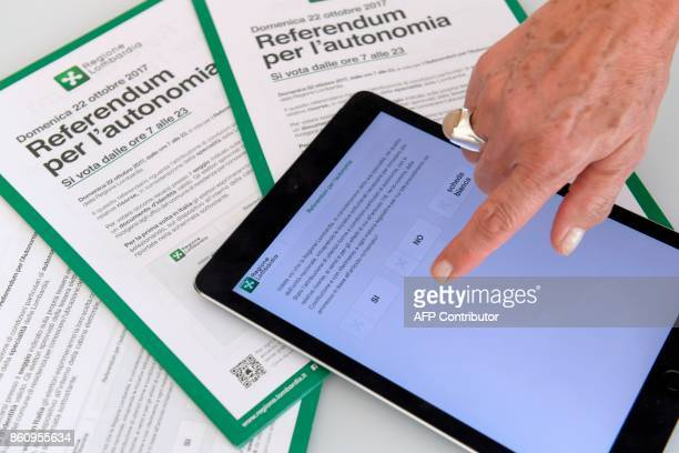 A person shows an App that will allow to vote for a referendum in Italy's northern region of Lombardy to request more autonomy from central...