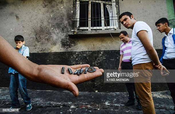 TOPSHOT A person shows pieces of projectile near the explosion scene following a late night attack on a wedding party that left at least 30 dead in...