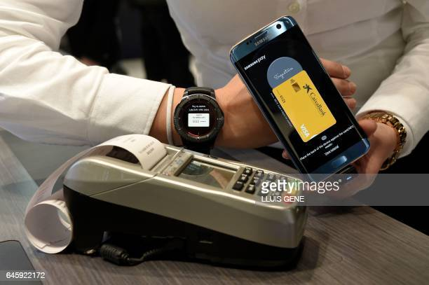 A person shows the 'Samsung Pay' system on the first day of the Mobile World Congress in Barcelonaon on February 27 2017 in Barcelona Phone makers...