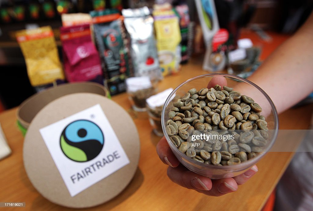 A person shows unroasted fairtrade coffee beans during the exhibition 'World of coffee', on June 27, 2013, in Nice, southeastern France.